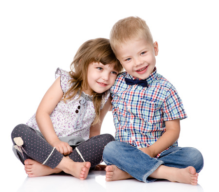 Smiling brother and little sister hugging  isolated on white background