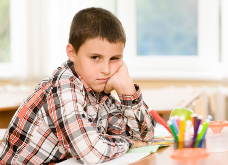 tired schoolboy in classroom Stock Photo