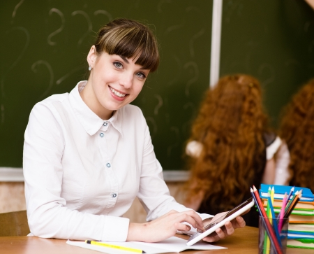 Teacher holding a tablet computer at classroom  looking at camera Stock Photo - 22418863
