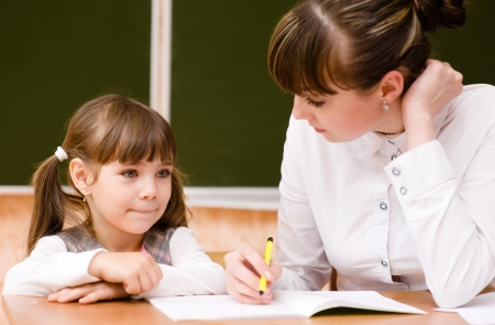 helps: Teacher helps the student with schoolwork in  classroom Stock Photo