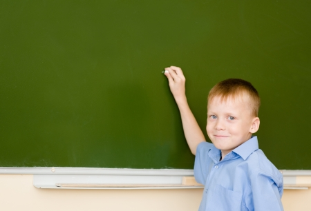 schoolboy holding a white chalk about to write photo