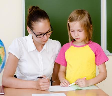grade schooler: Teacher helps the student with schoolwork in school classroom Stock Photo
