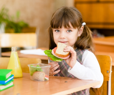 having lunch: portrait schoolgirl looking at camera while having lunch during Stock Photo