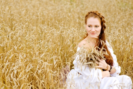 Young woman in white dress sitting in field with wheat photo