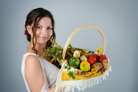 young pregnant woman with wicker basket harvest  looking at camera photo