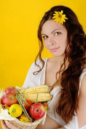 woman holds a basket of fruit and vegetables  looking at camera photo