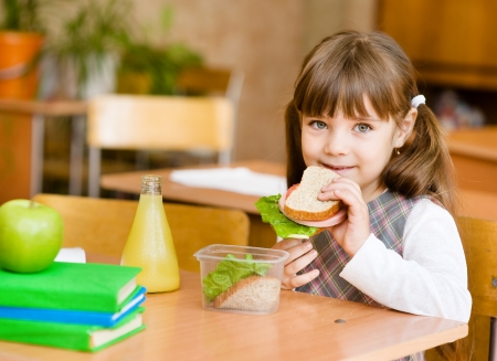 lunch break: portrait schoolgirl looking at camera while having lunch during Stock Photo