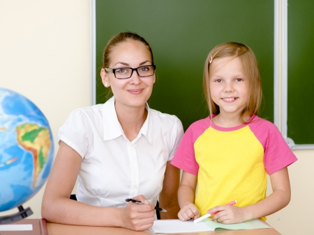 Teacher helping schoolgirl with schoolwork in classroom photo
