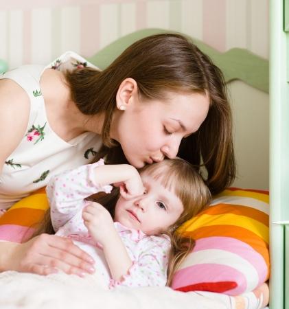 enfant malade: m�re embrassant un enfant malade