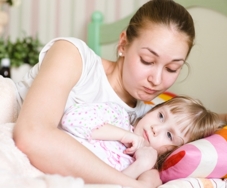 mother embraces the sick child photo