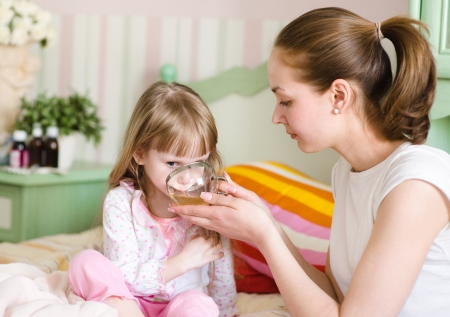 baby sick: mother gives to drink to the sick child Stock Photo