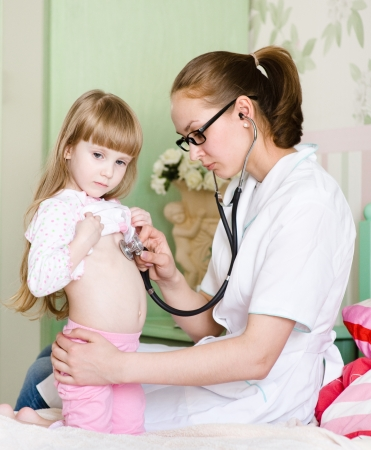 doctor examining girl with stethoscope photo