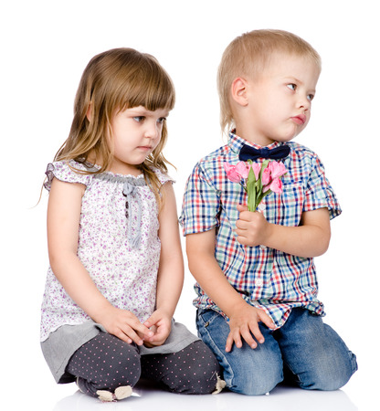resentful: resentful boy gives to the girl a flower  isolated on white background Stock Photo