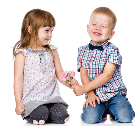 Little boy giving flowers to girl  isolated on white background