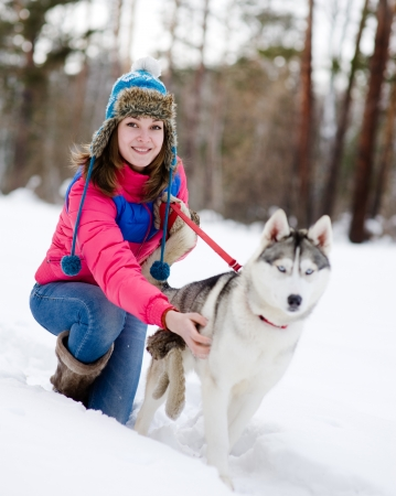 Girl with her cute dog in the winter forest photo