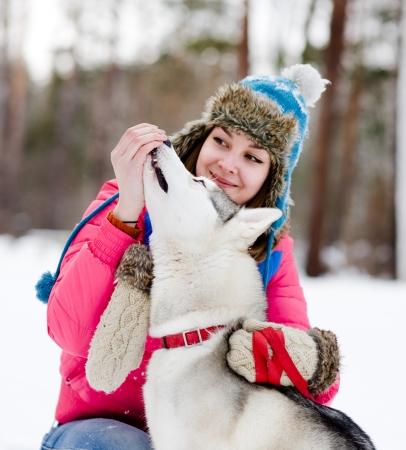 girl feeding her husky dog photo