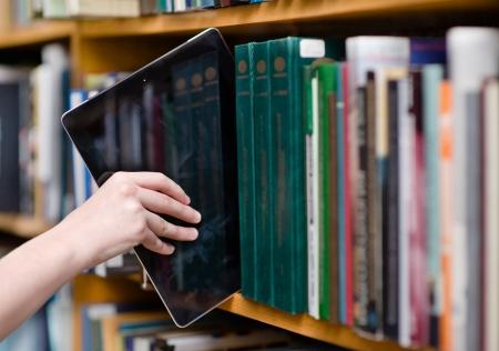 plan rapproché de main mettre un Tablet PC dans les rayons de la bibliothèque