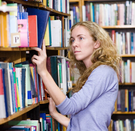 girl selecting book from a bookshelf photo