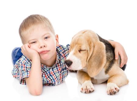 Sad boy hugging beagle puppy  isolated on white background photo