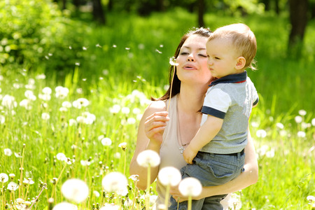 Mother and baby boy blowing on a dandelion photo