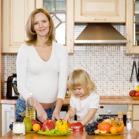 pregnant mother and daughter in kitchen photo