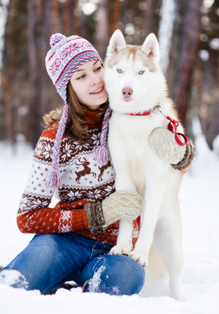 teen girl embracing cute dog in winter park photo
