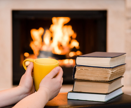 hands holding cup of coffee near the fireplace photo