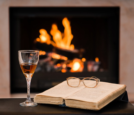 glass of cognac and book by the fireplace photo