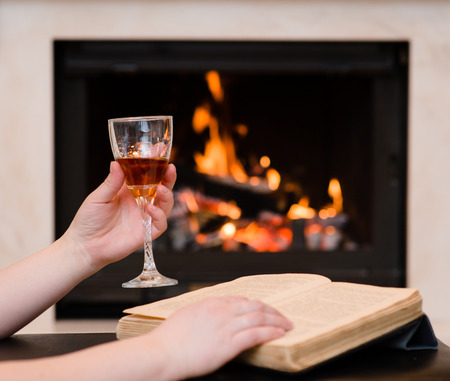 hands holding glass of cognac and book by the fireplace photo