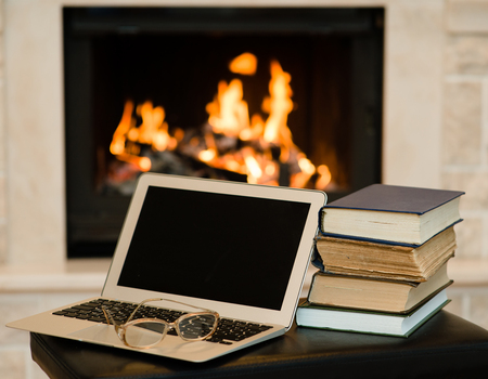 laptop and pile of books against the background of the fireplace photo