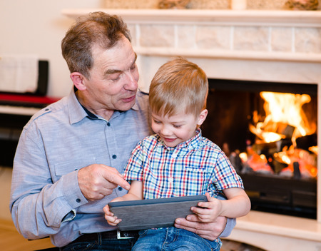 Happy boy and his grandfather using a tablet computer photo