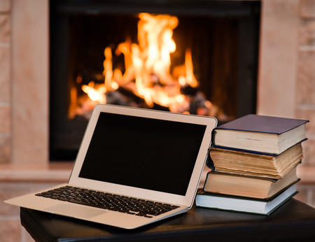 tutorials: laptop and pile of books against the background of the fireplace Stock Photo