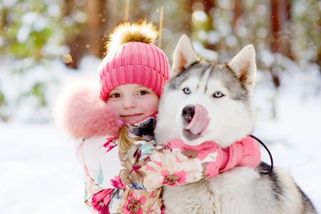 girl hugging Huskies in winter forest photo