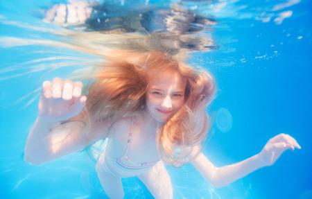 Smiling blonde haired teen girl underwater photo
