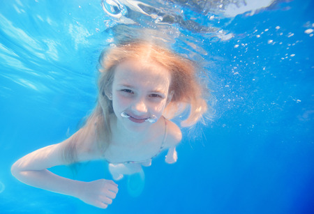 Swimming young girl underwater in pool photo