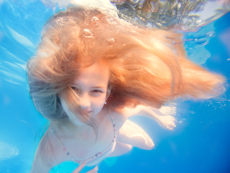 Swimming young girl with long haired underwater in pool photo