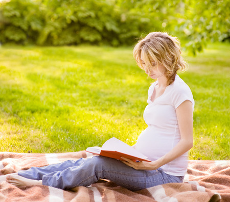 Pregnant woman reading a book photo