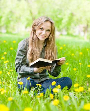 girl sitting on grass with dandelions reading a book and looking at camera photo