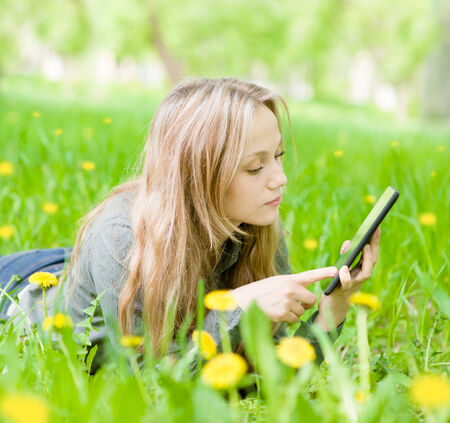 beautiful girl lying on the grass and using tablet computer photo