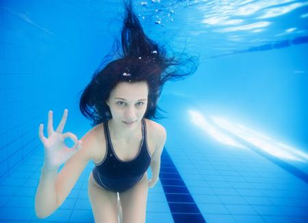 girl underwater: jong meisje onderwater tonen ok teken