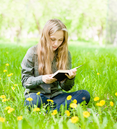 girl sitting on grass with dandelions and reading a book photo