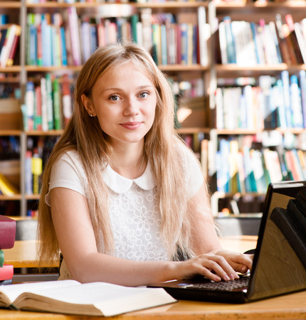 Portrait of a pretty female student with laptop in library photo