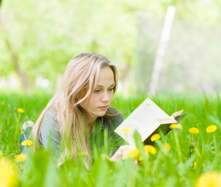 Pretty young woman lying on grass with dandelions and reading a photo