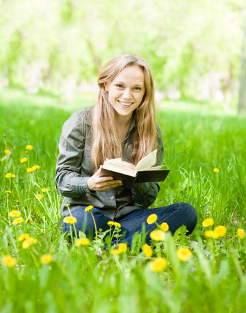 laughing girl sitting on grass with dandelions reading a book and looking at camera photo