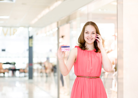 Beautiful young woman with credit card  In shopping mall photo