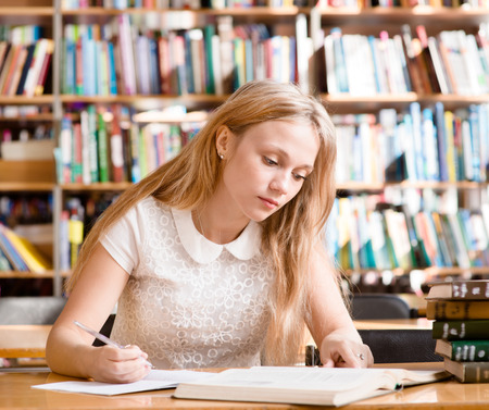 assignments: young female student doing assignments in library