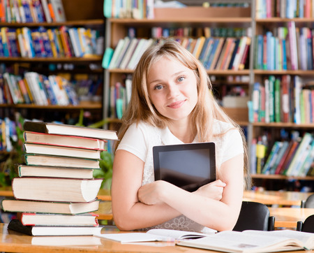 girl with tablet computer in library photo
