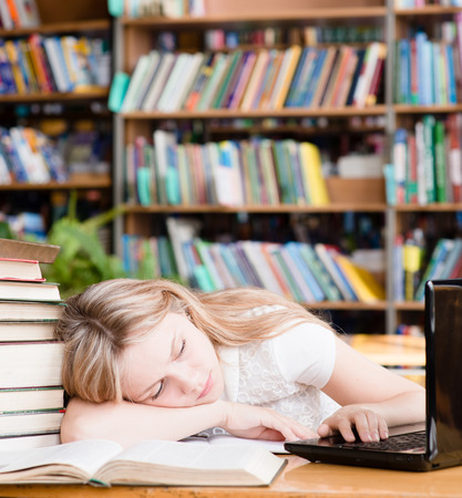 pretty female student sleep in library photo