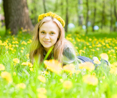 portrait beautiful girl with a wreath of dandelions lying on the grass photo