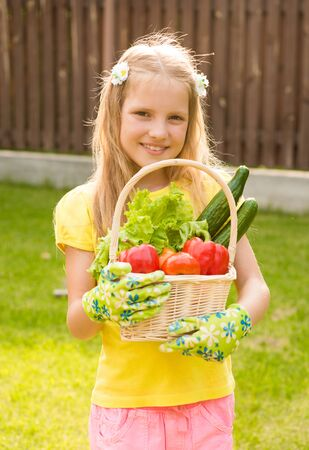 beautiful little girl with vegetables in basket photo